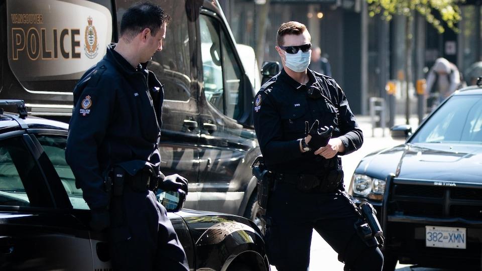 Deux policiers de Vancouver au centre-ville. L'un d'eux porte un masque.