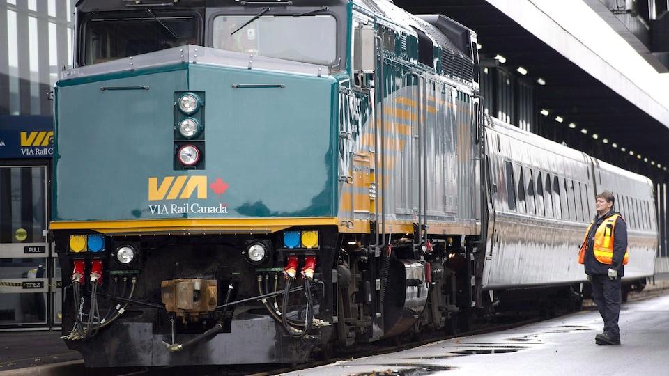 Photo d'un employé vêtu d'un dossard orange à côté d'une locomotive verte tirant deux wagons dans une gare