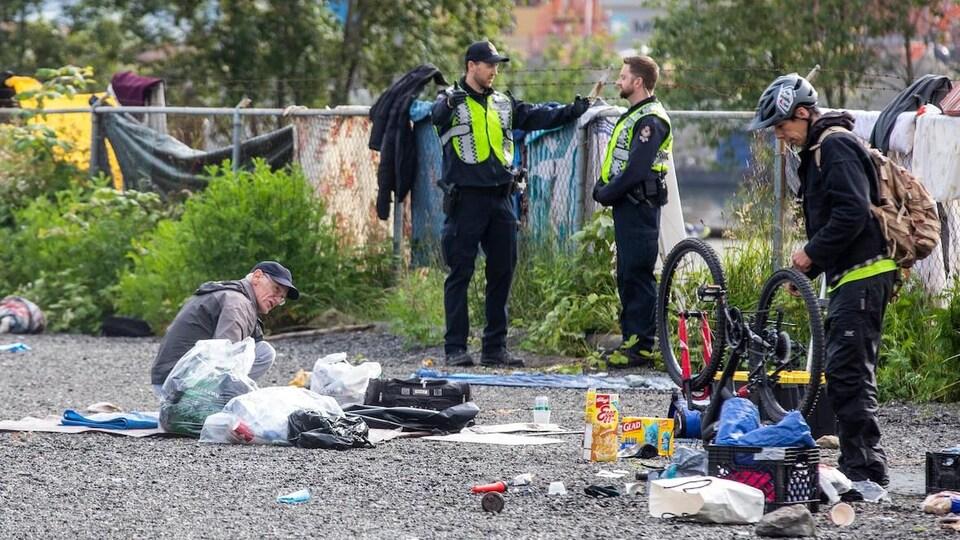 Deux policiers discutent tandis que deux campeurs ramassent leurs biens.