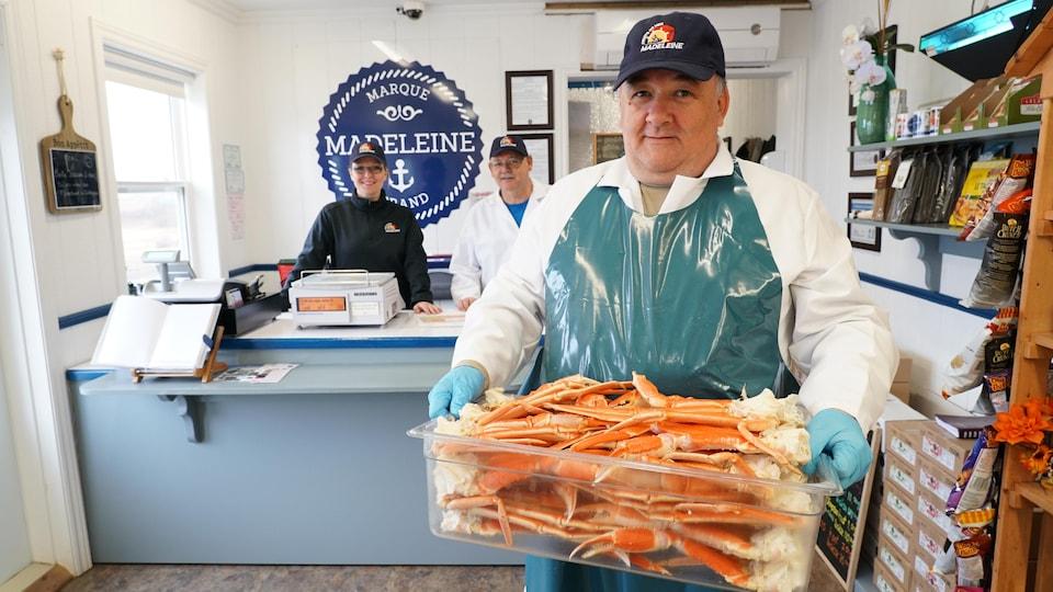 Un employé de Fruit de mer Madeleine avec un contenant rempli de section de crabes. Derrière, on peut voir deux de ces collègues de la poissonnerie.