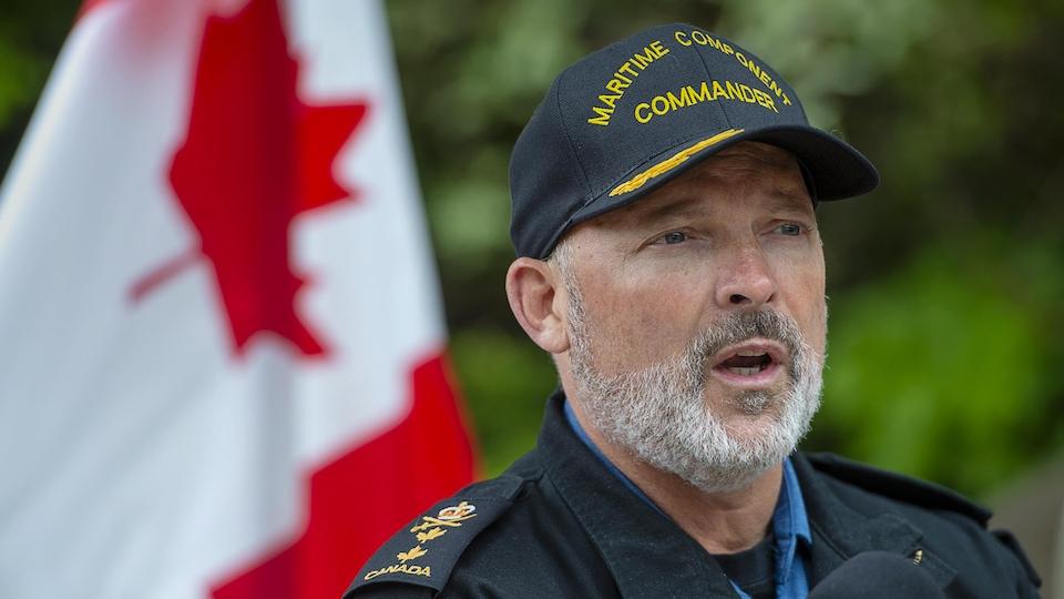 Un homme portant la barbe et une casquette parle devant un drapeau du Canada, à l'extérieur.