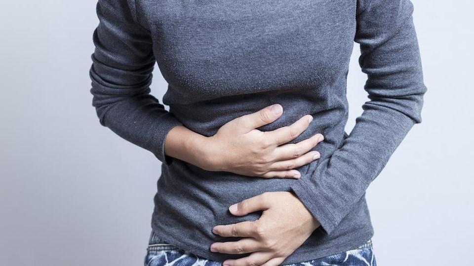 Une femme se tient le ventre et semble avoir mal.