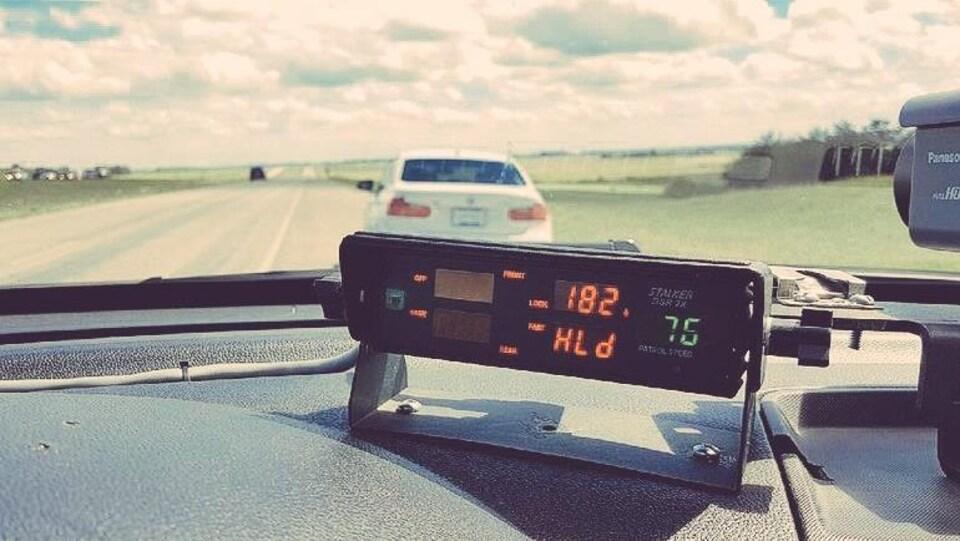Vue depuis la place conducteur de la voiture de police, le radar au premier plan indique la vitesse de 182 km/h. En arrière plan, de l'autre côté du parre-brise, se trouve une voiture blanche stationnée sur le bas-côté.