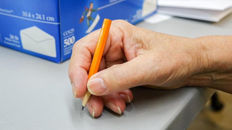 Une femme tient un crayon de vote.