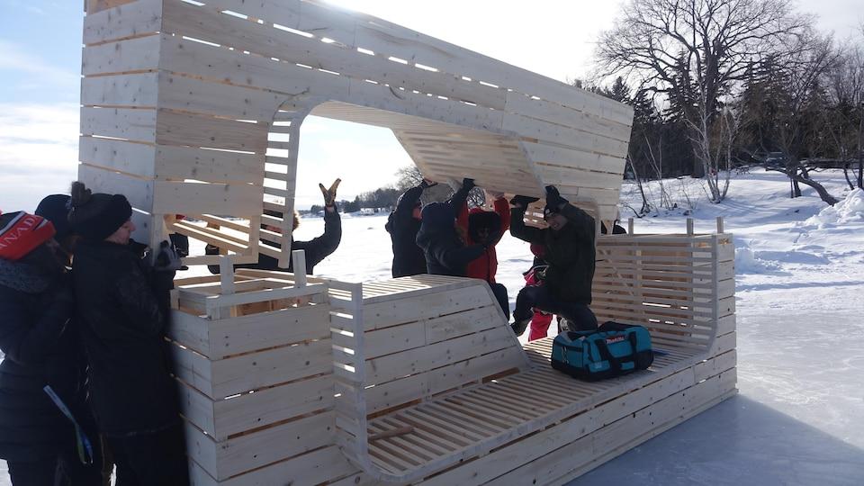 Un groupe de personnes soulèvent une structure en bois pour l'installer sur une base.