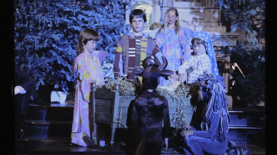 Enfants déguisés en Marie, Joseph, boeuf, âne et anges, qui entourent le petit Jésus.