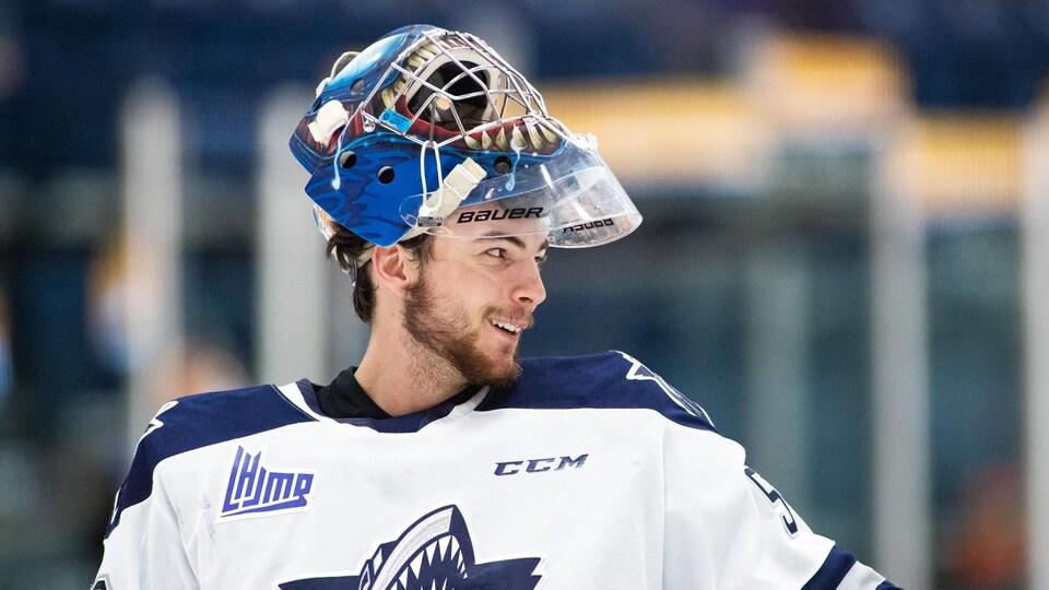Un joueur de l'Océanic a son casque de hockey relevé sur le bout de sa tête.