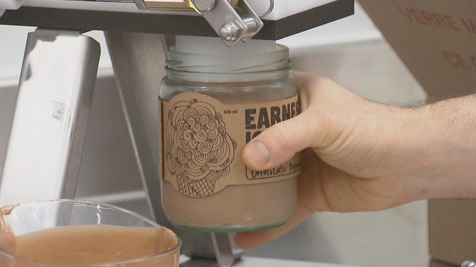 Un pot de crème glacée est rempli par une machine