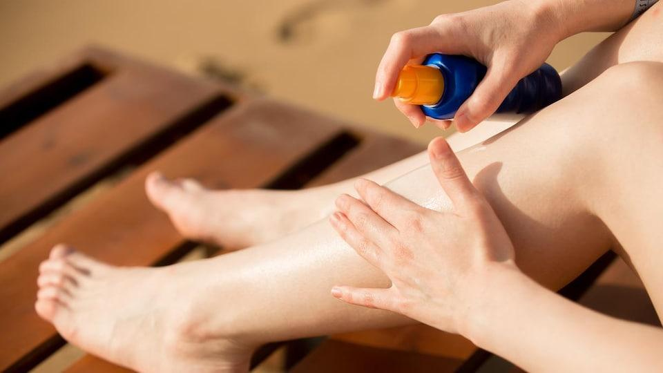 Une femme s'applique de la crème solaire sur les jambes.