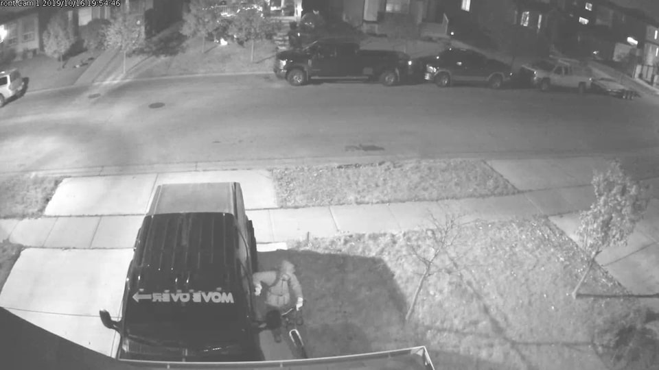 Une image en noir et blanc montre un homme en train d'essayer d'ouvrir la portière d'une voiture.