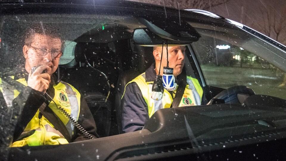Deux hommes dans une voiture. Le passager tient un appareil de communication radio.