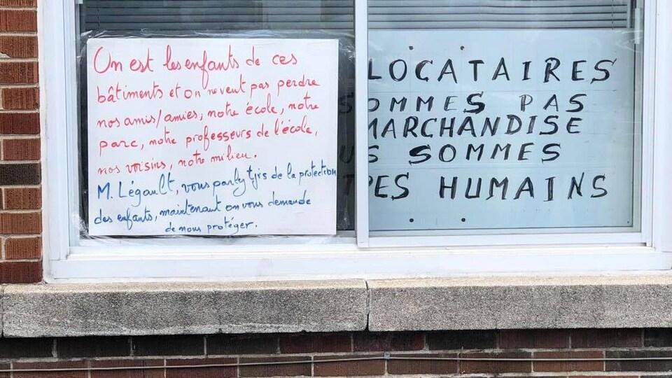 Une affiche dénonçant les rénovictions placardée sur une fenêtre d'un immeuble.