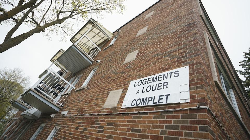Une affiche accrochée à un immeuble sur laquelle il est écrit : logement à louer, complet.