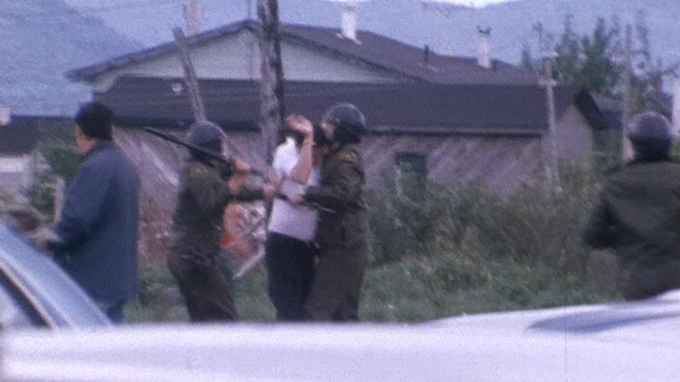 Un Mi'gmaw est immobilisé par un policier alors qu'un agent tient une matraque, prêt à le frapper.