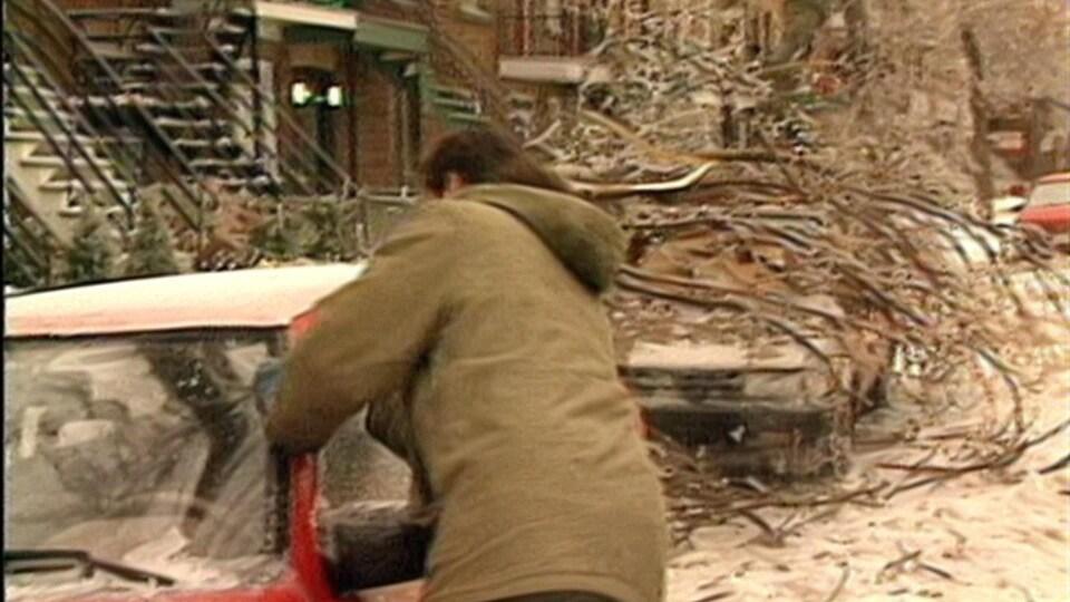 Un automobiliste tente de gratter l'épaisse couche de glace qui recouvre son véhicule. Juste derrière, un arbre couvert de glace s'est écrasé sur une voiture dans une rue de Montréal.