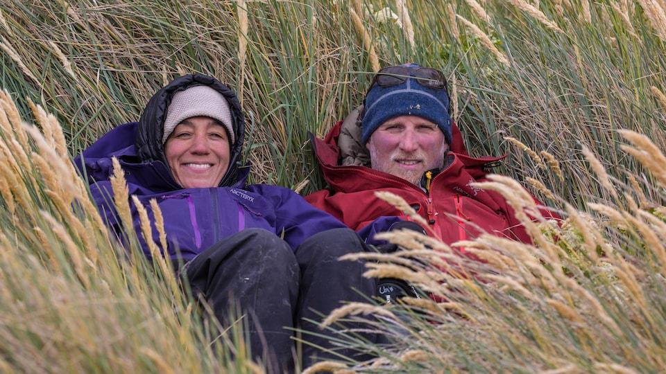 Une femme et un homme assis dans l'herbe.