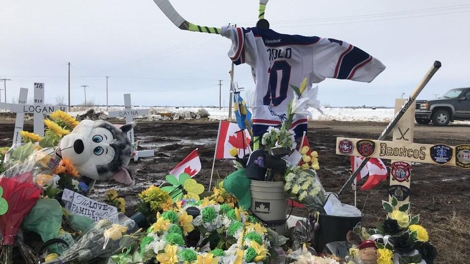 Bâtons de hockey placés en croix, revêtus d'un chandail de hockey. Croix et fleurs.