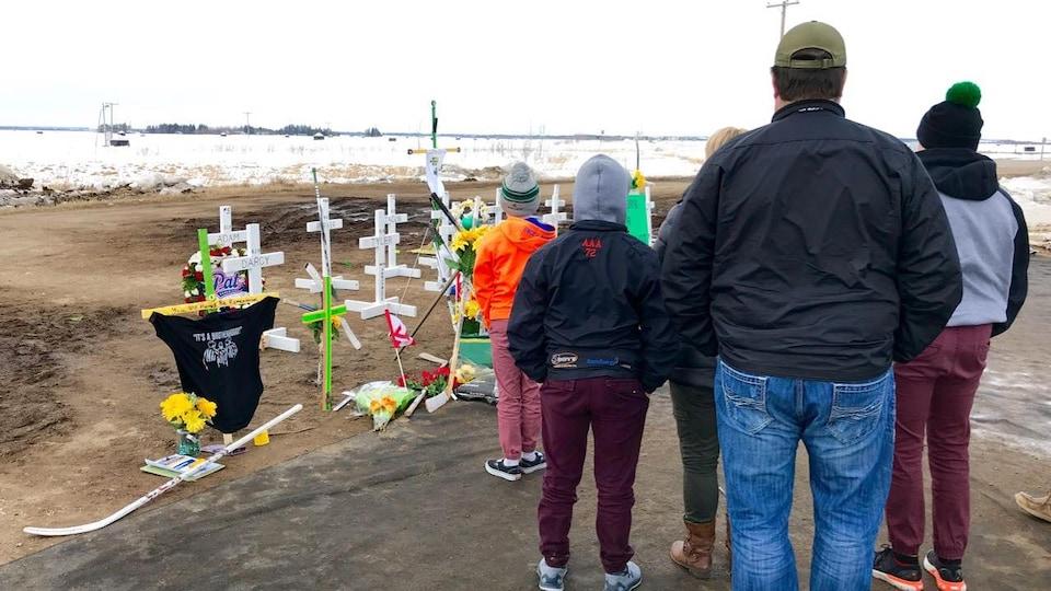 Une famille regarde les croix décorées de fleurs, chandails de hockey et drapeaux.