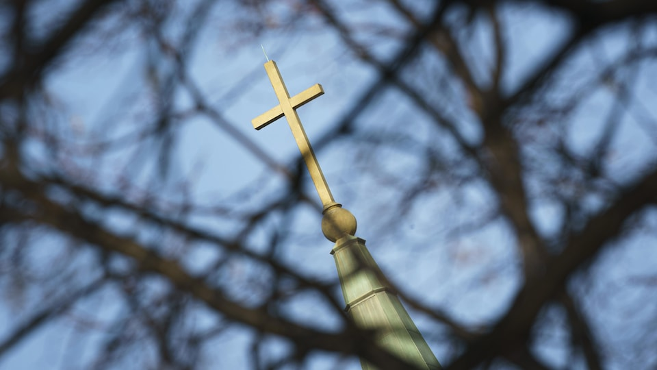 Une croix au sommet du clocher d'une église catholique à Montréal.
