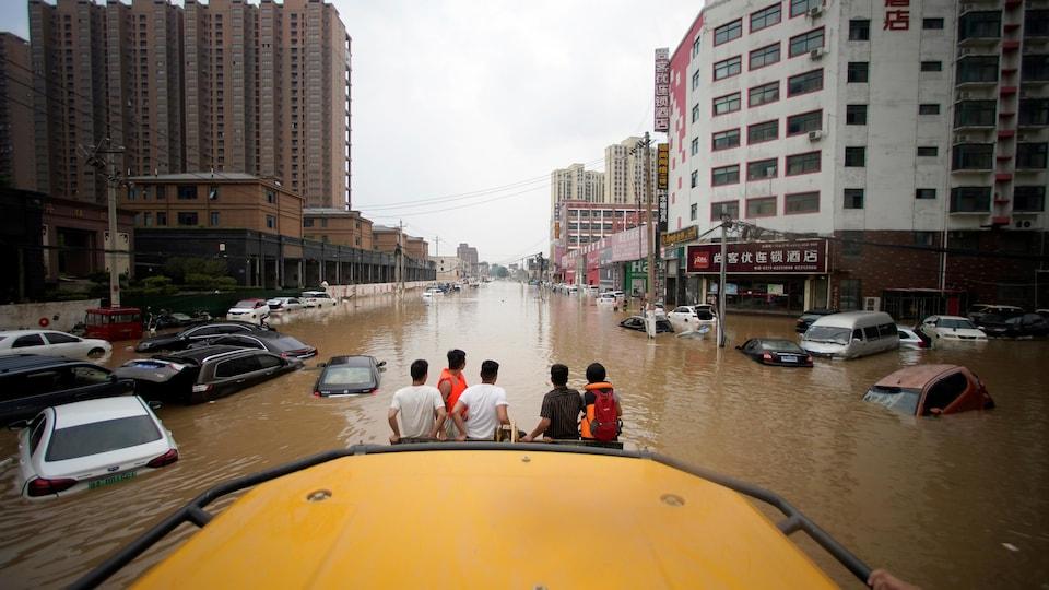 Cinq personnes, vues de dos, regardent une rue inondée depuis la pelle d'une chargeuse frontale.