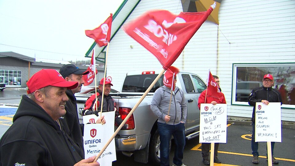 Des manifestants avec différentes pancartes et des drapeaux rouges avec le logo d'Unifor