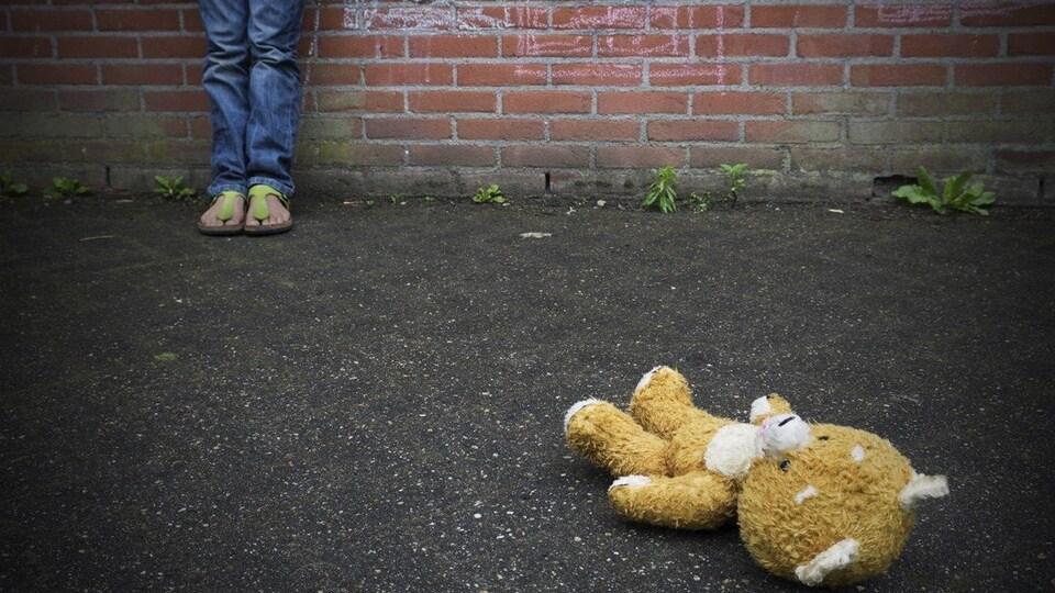 Un ourson de peluche au sol avec des pieds d'enfants au loin
