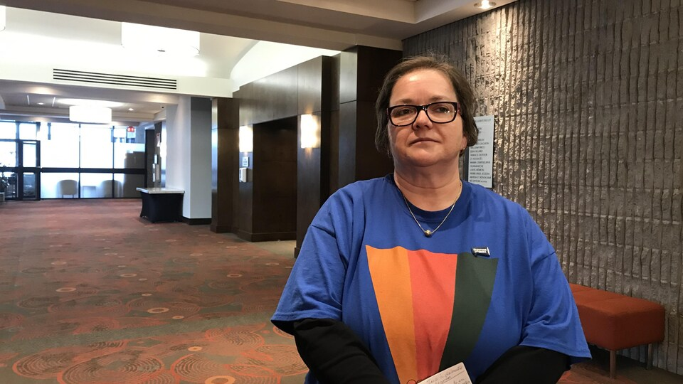 Une femme pose dans un corridor d'hôtel.