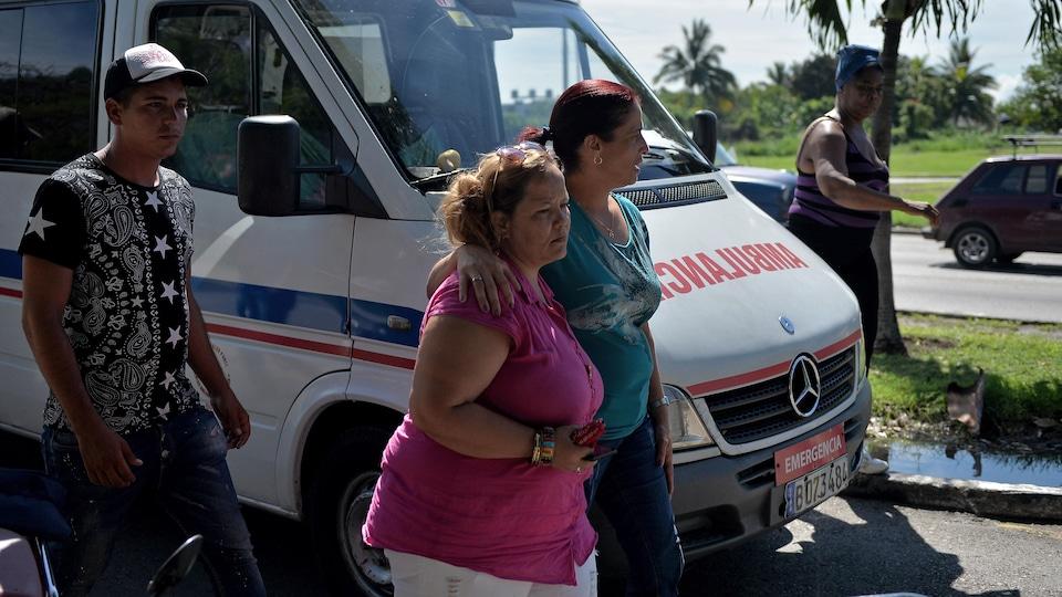 Des Cubains marchent à côté d'une ambulance.