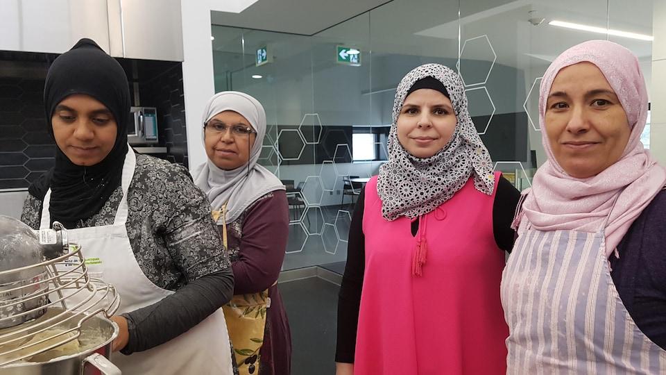 Quatre femmes sont à l'œuvre dans une cuisine communautaire.