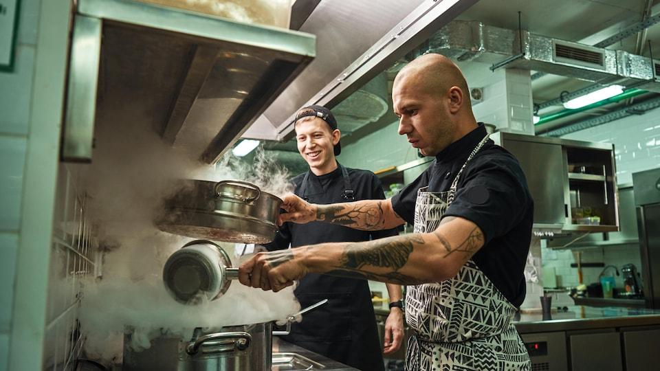 Un chef cuisinier et son assistant dans une cuisine de restaurant.