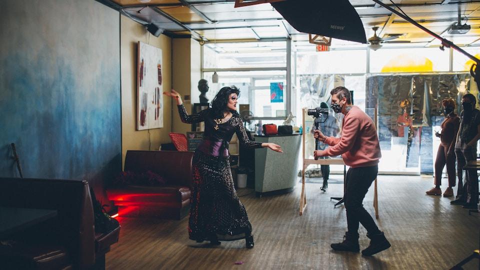 Un artiste drag effectuant une performance devant un videographe masqué.