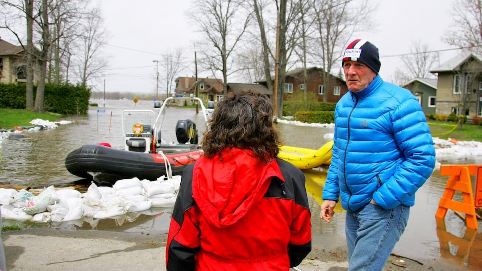 Des personnes devant des bateaux sur une rue résidentielle inondée