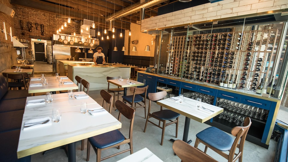 La salle à manger du restaurant ARVI avec des tables et des bouteilles de vin dans un grand espace vitré.