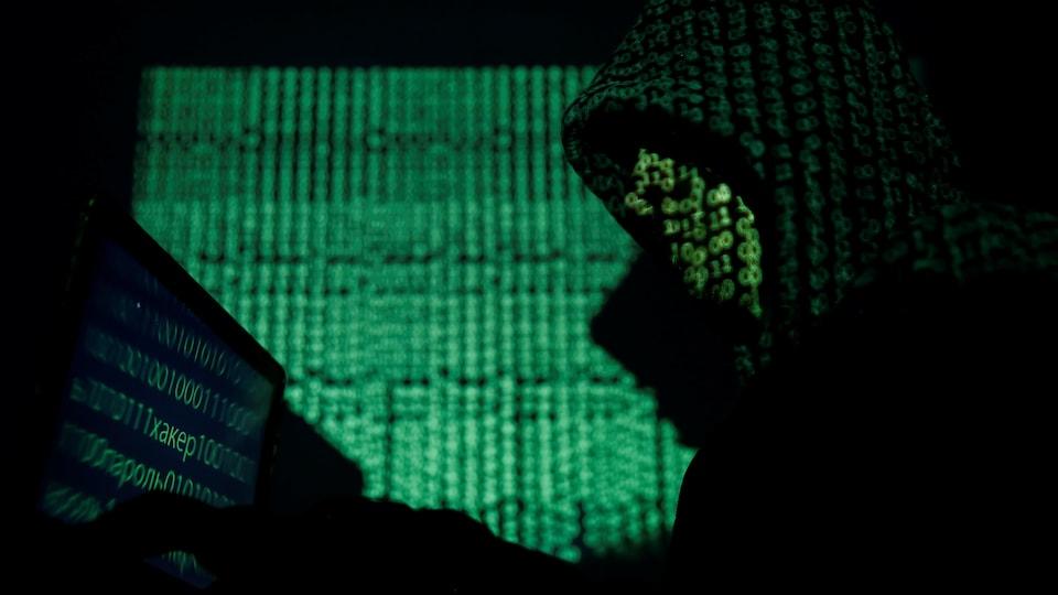Un homme portant un capuchon, dont le visage est remplacé par du code informatique, est assis devant un écran où l'on voit aussi du code informatique.