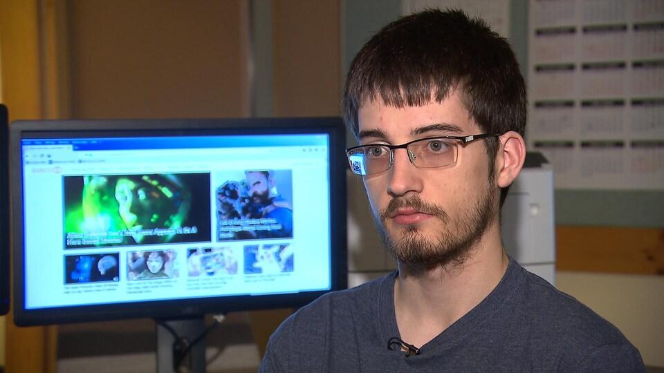 Cédric Vibert répond à des questions assis à un bureau devant un ordinateur allumé.