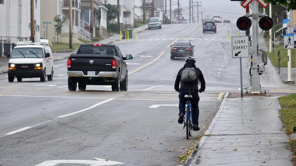 Un cycliste et des véhicules circulent sous la pluie, à Rimouski.