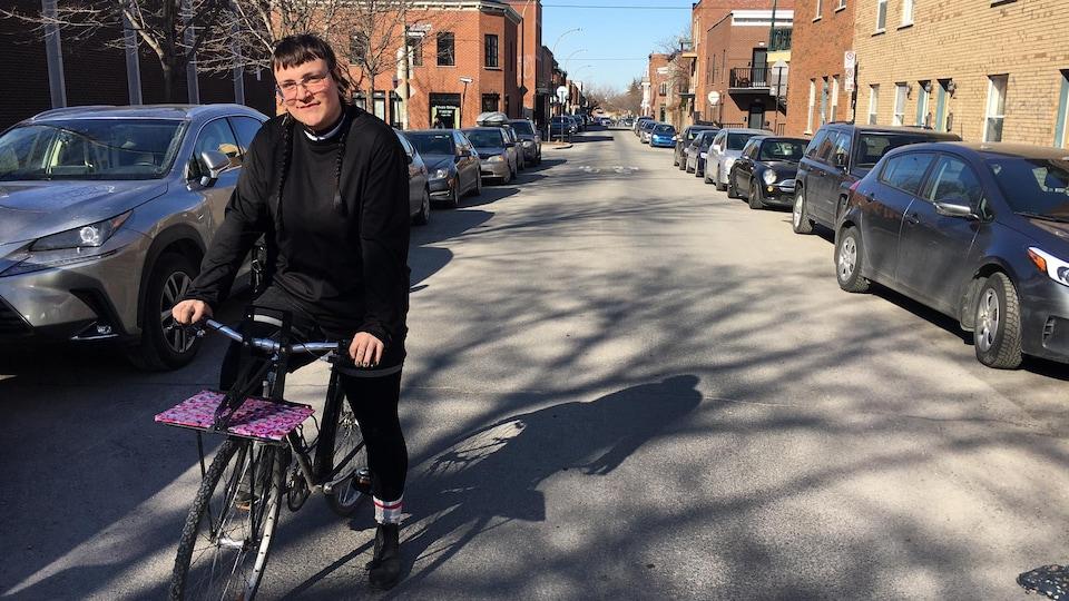 Un livreur sur son vélo, dans une rue de Montréal, ensoleillée