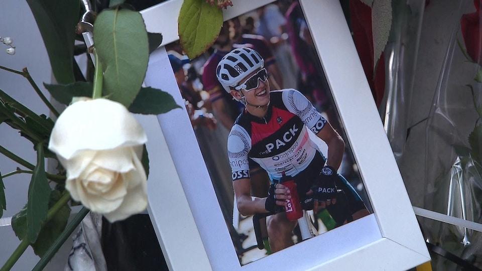 Photo du cycliste Clément Ouimet accrochée sur un poteau de la voie Camillien-Houde, sur le mont Royal, avec une rose blanche.