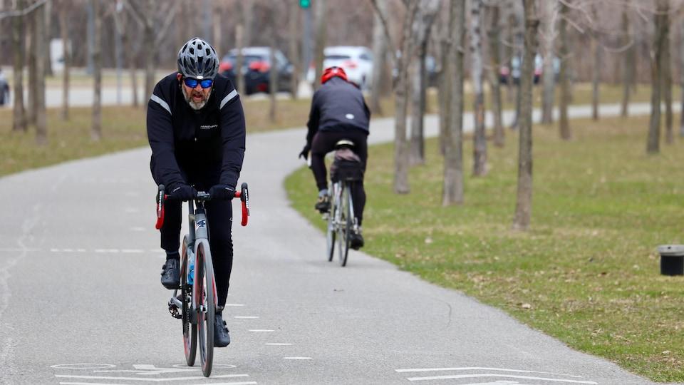 L'homme croise un autre cycliste sur la piste, le long d'une rue.
