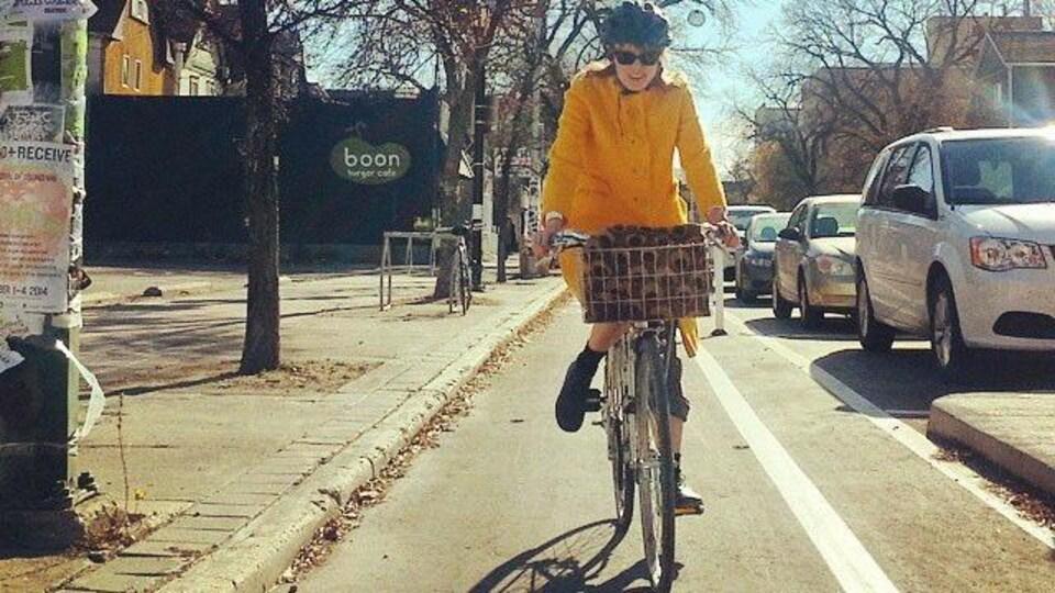 Une femme en vélo sur une voie cyclable à Winnipeg.