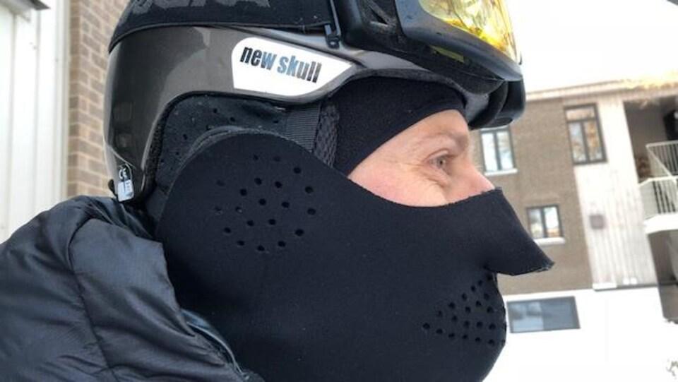 Un cycliste porte un casque, des lunettes et un cache-nez