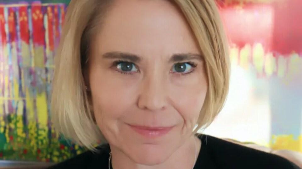 Cynthia Carr est derrière un fond coloré. Elle a les cheveux courts blonds.