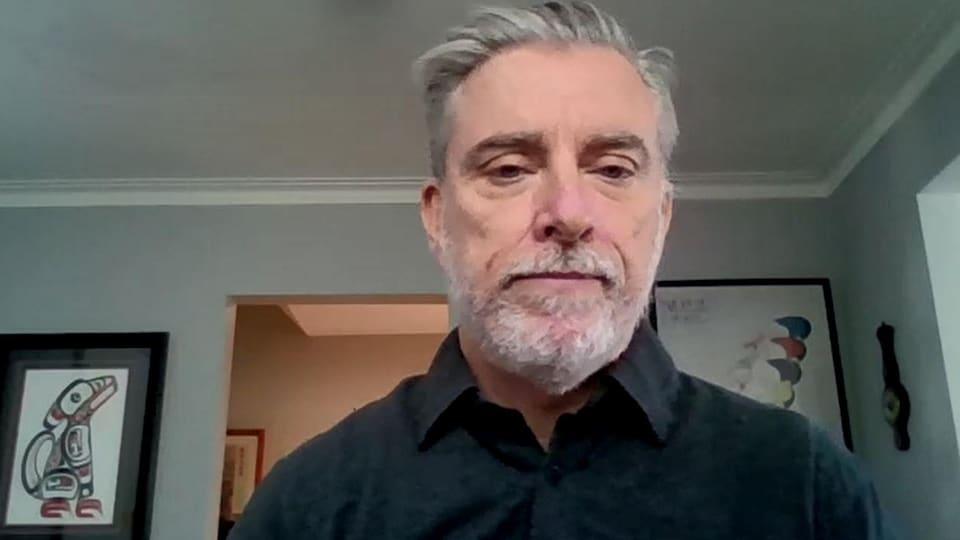 Un homme, dans son salon, en vidéoconférence.