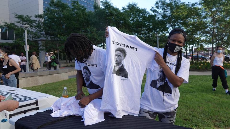 Une manifestante tient un t-shirt qui porte le message : « Que justice soit faite pour Dafonte ».