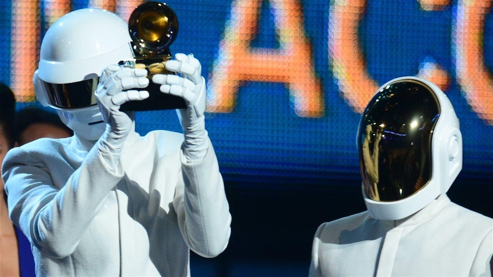 Les deux hommes sont vêtus de blanc et portent chacun un casque intégral qui leur cache le visage. Un des deux tient un trophée dans ses mains.