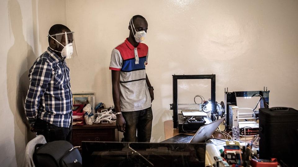 Deux hommes portant des masques de protection dans un bureau.