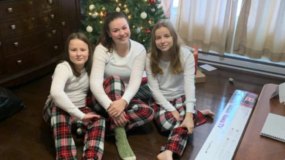 Les trois jeunes devant un sapin de Noël.
