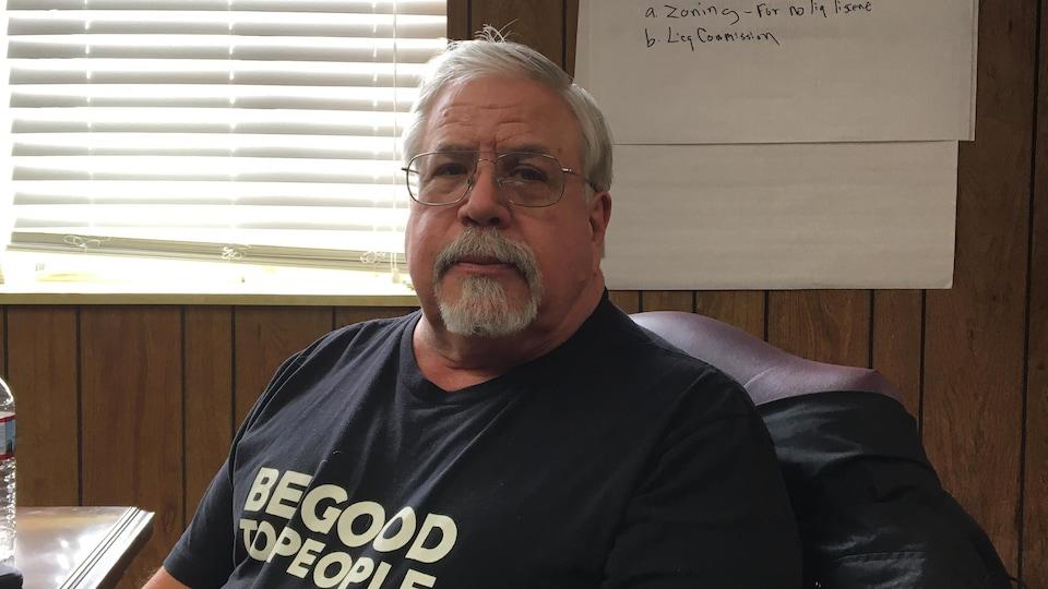 Un homme à la moustache et portant des lunettes regarde la caméra.