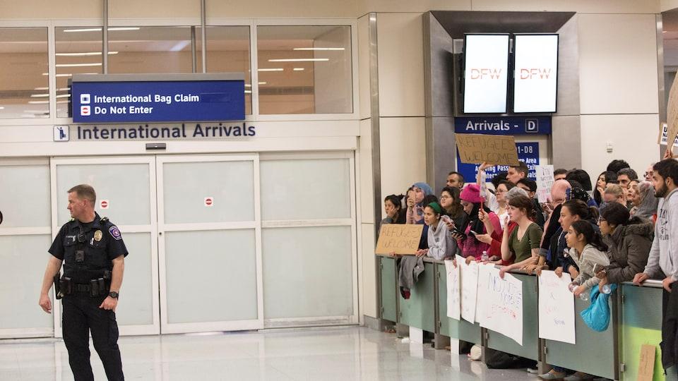 Des manifestants rassemblés pour protester contre le décret imposé par le président des États-Unis, Donald Trump à l'aéroport international de Dallas/Fort Worth.