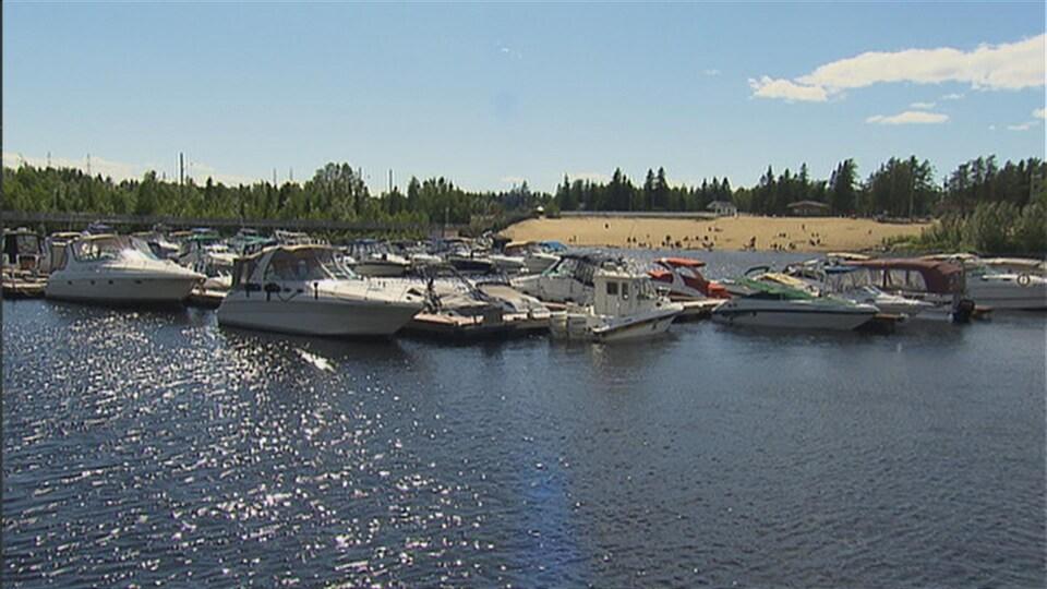 Des bateaux sont accostés à un quai. Derrière, il y a une plage avec des personnes.